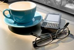 Coffee break. Pda,coffee cup and eyeglasses Royalty Free Stock Image