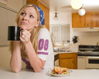 Coffee Break. Blond caucasian woman leaning on counter in kitchen holding a cup of coffee with sandwich near ooking up Stock Photo