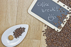 Coffee break. Coffee beans with cookies on a white plate and a board Stock Photography