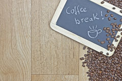 Coffee break. Coffee beans on wood with a chalkboard as a symbol for coffee break Royalty Free Stock Photos