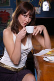 Coffee break. Young woman drinking coffee in a restaurant Royalty Free Stock Photography