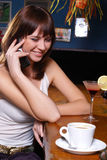 Coffee break. Young woman drinking coffee and laking on mobile in a restaurant Royalty Free Stock Photo