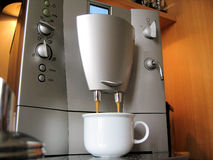 Coffee break. Filling a white coffee cup with fresh coffee from a coffee / espresso machine stock image