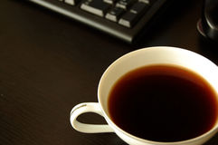 Coffee break. Coffee cup on desk by computer Royalty Free Stock Photo