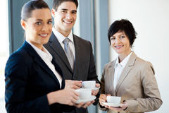Coffee break. Group of businesspeople having coffee during break in office stock image