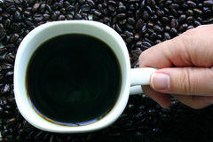 Coffee Break. This is the top view of a hand grabbing a mug of coffee surrounded by coffee beans. Would be ideal for a Coffee Break sign Royalty Free Stock Images
