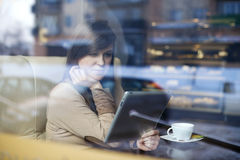 Coffee break. Young woman using tablet in coffee shop Stock Photo