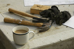 Coffee Break. Coffee cup at construction site with suggestion of tools in the background Royalty Free Stock Photos