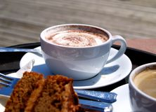 Coffee Break. Coffees and cake on a table of an outdoor cafe in the sun Stock Photography