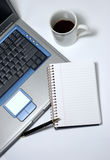 Coffee Break. A cup of black coffee, laptop, notepad and pen royalty free stock images