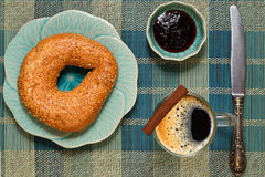 Coffee break with bagel and jam. Coffee added cinnamon with fresh bagel and cranberry jam royalty free stock photo