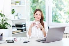 Coffee break. Beautiful young woman having a coffee break in office Stock Image