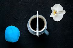 Coffee break, blue glazed donut and ceramic cup with coffee on dark background with orchid flower,copy space, closeup royalty free stock photo