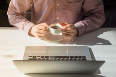 Coffee break in bright office. Male hands hold cup of steaming hot coffee next to laptop computer in minimalistic indoor room on sunny day royalty free stock image