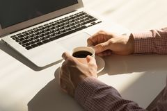 Coffee break in bright office. Male hands hold cup of steaming hot coffee next to laptop computer in minimalistic indoor room on sunny day royalty free stock photos