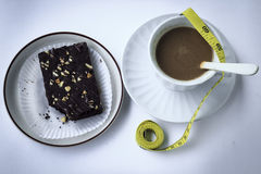 Coffee break with brownies waist and measuring tape. Drink at the dawn of middle age. Strengthen energy, but fat stock images