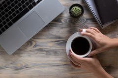 Coffee break. Close-up top view of hands holding cup with coffee. Coffee break. Close-up top view of hands holding cup with coffee while sitting at the wooden stock photos