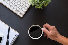 Coffee break. Close-up top view of hands holding cup on work desk. Royalty Free Stock Photos