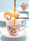 Coffee break. Coffee is being poured into vintage rose pattern cup Royalty Free Stock Photos