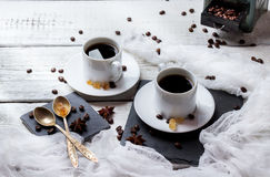 Coffee break concept. Cups and beans, breakfast theme. Breakfast, food, still life, coffee break concept. Cup with black coffee and beans on a rustic white stock images
