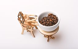Coffee break concept. Mug fresh roasted coffee beans looks giant on tiny table. Cup of coffee beans little decorative. Table with chair and wooden model of stock image