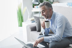 Coffee break. Confident businessman at home, he is having a coffee break in the living room and networking with his laptop Stock Photos