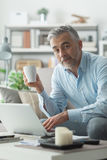 Coffee break. Confident businessman at home, he is having a coffee break in the living room and networking with his laptop Royalty Free Stock Photography