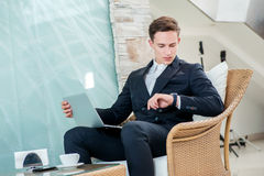 Coffee break. Confident and successful businessman sitting in an Stock Photos