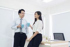 Coffee break. Couple of young colleagues in formal wear standing. At workplace office, Businessman and businesswoman drinking coffee stock photos