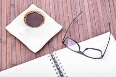 Coffee break. Cup of coffee with glasses and notebook on a wooden background made of bamboo Stock Photos