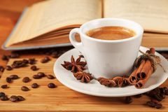 White Cup of coffee espresso surrounded by of roasted coffee beans, cinnamon, anise and an open book on a wooden table stock photography