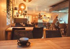 Coffee break with cup on table of restaurant or cafe. Interior bar lonly drinking visitor.  royalty free stock photography