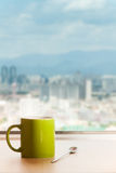 Coffee Break watching landscape. A cup of coffee on the table with a tea spoon. A view of city upon the table Stock Photo