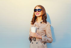Coffee break! Fashion portrait pretty smiling woman holds cup wearing a coat black sunglasses over sunny grey. Background Royalty Free Stock Photo