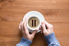 Coffee break. Female hands in sleeves of cozy blue pullover touches white cup of classic coffee, top view, close up stock photos