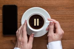 Pause icon, coffee break, stop sign. Female hands touches white cup of espresso coffee, top view, wooden background royalty free stock photos