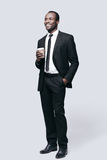 On coffee break. Full length of handsome young African man looking away and smiling while standing against grey background Stock Photography