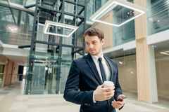 Confident man holding coffee cup and using his smart phone while walking in hall. Coffee break on go. confident man holding coffee cup and using his smart phone Royalty Free Stock Photos