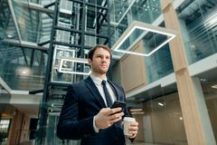 Confident man holding coffee cup and using his smart phone while walking in hall. Coffee break on go. confident man holding coffee cup and using his smart phone Royalty Free Stock Image