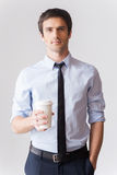 Coffee break. Handsome young man in shirt and tie holding coffee cup and looking at camera while standing against grey background Stock Images