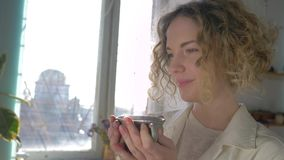 Coffee break of happy smiling painter woman with cup hot drink enjoying creative process against sunlit window stock footage