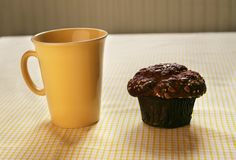 Coffee Break and Honey Nut Muffin. Conceptual country style living, - image of a honey nut muffin and coffee mug on a country style yellow checkered table cloth stock photo