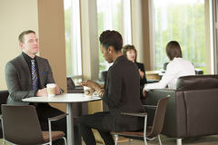 Coffee break. Horizontal, color image of employees in the break room and lounge talking and having a cup of coffee stock photography