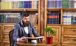 Coffee break, leisure concept. Education and intelligence. Hipster sits in vintage interior and enjoys literature. Bearded man in formal wear in library stock images