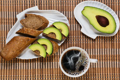 Coffee break with light healthy snack. Big cup with espresso coffee and some simple sandwiches with avocado royalty free stock photography