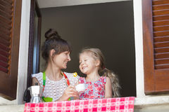 Coffee-break with lollipop sweet of mother with daughter Royalty Free Stock Photos