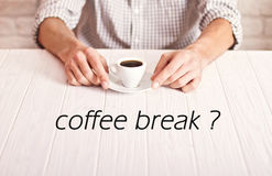 Coffee break. Man sitting on the white table with cup of espresso in the checked shirt. White bricks wall background Stock Photo