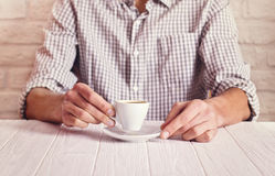 Coffee break. Man sitting on the white table with cup of espresso in the checked shirt. White bricks wall background Stock Image