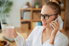 Coffee Break in Modern Office. Profile view of pretty young businesswoman answering phone call while having coffee break in modern open plan office, head and stock image
