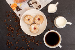 Coffee break. Morning breakfast. Cup of coffee and cookies. Coffee break. Cup of coffee, saucer with cookies, milk jug, roasted coffee beans and culinary magazin Stock Photo